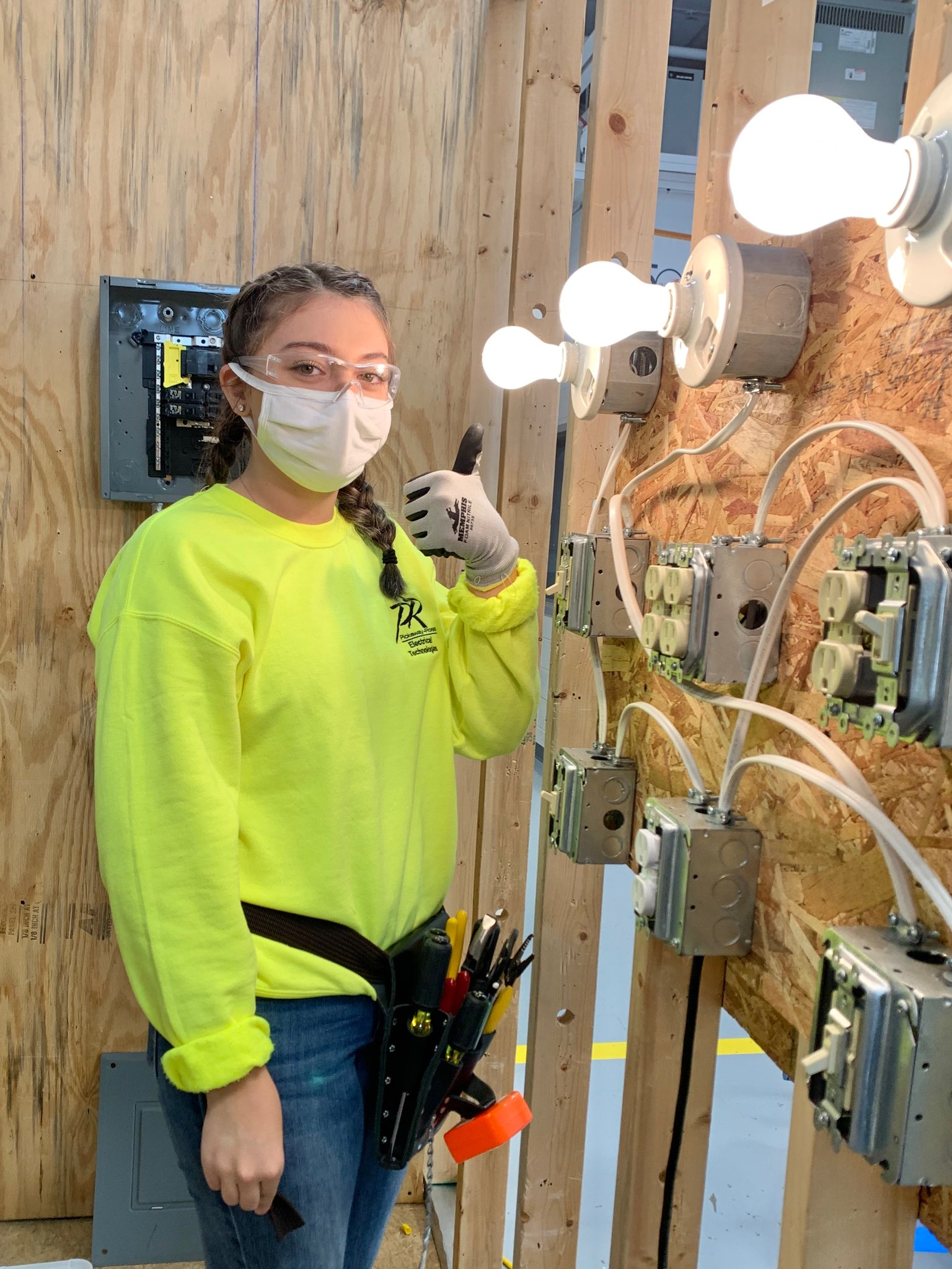 A girl in a yellow shirt and jeans stands with a thumbs up next to a light bulb and wiring.
