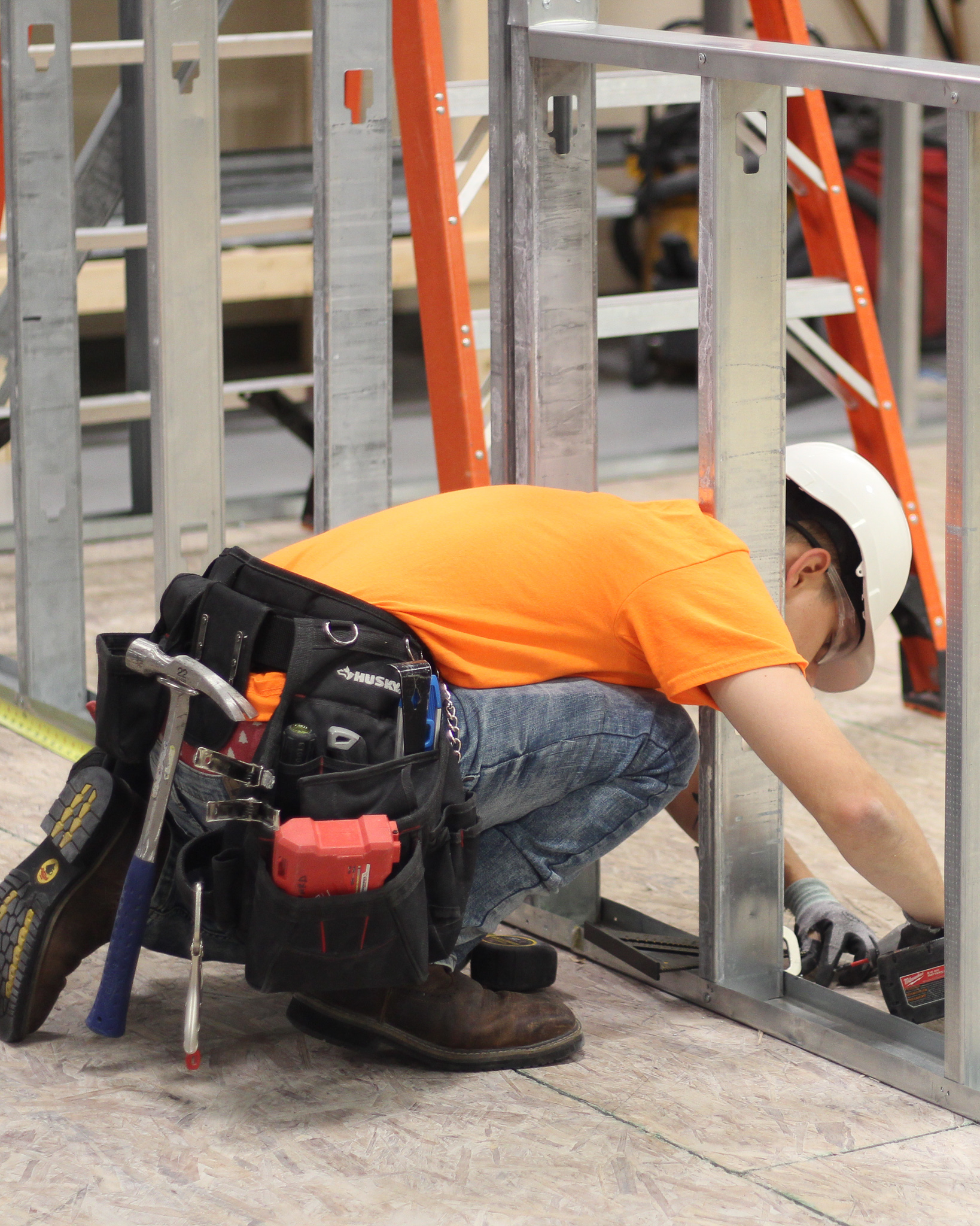 A boy in an orange shirt and jeans wears a toolbelt. He is using a drill to attach metal support beams.