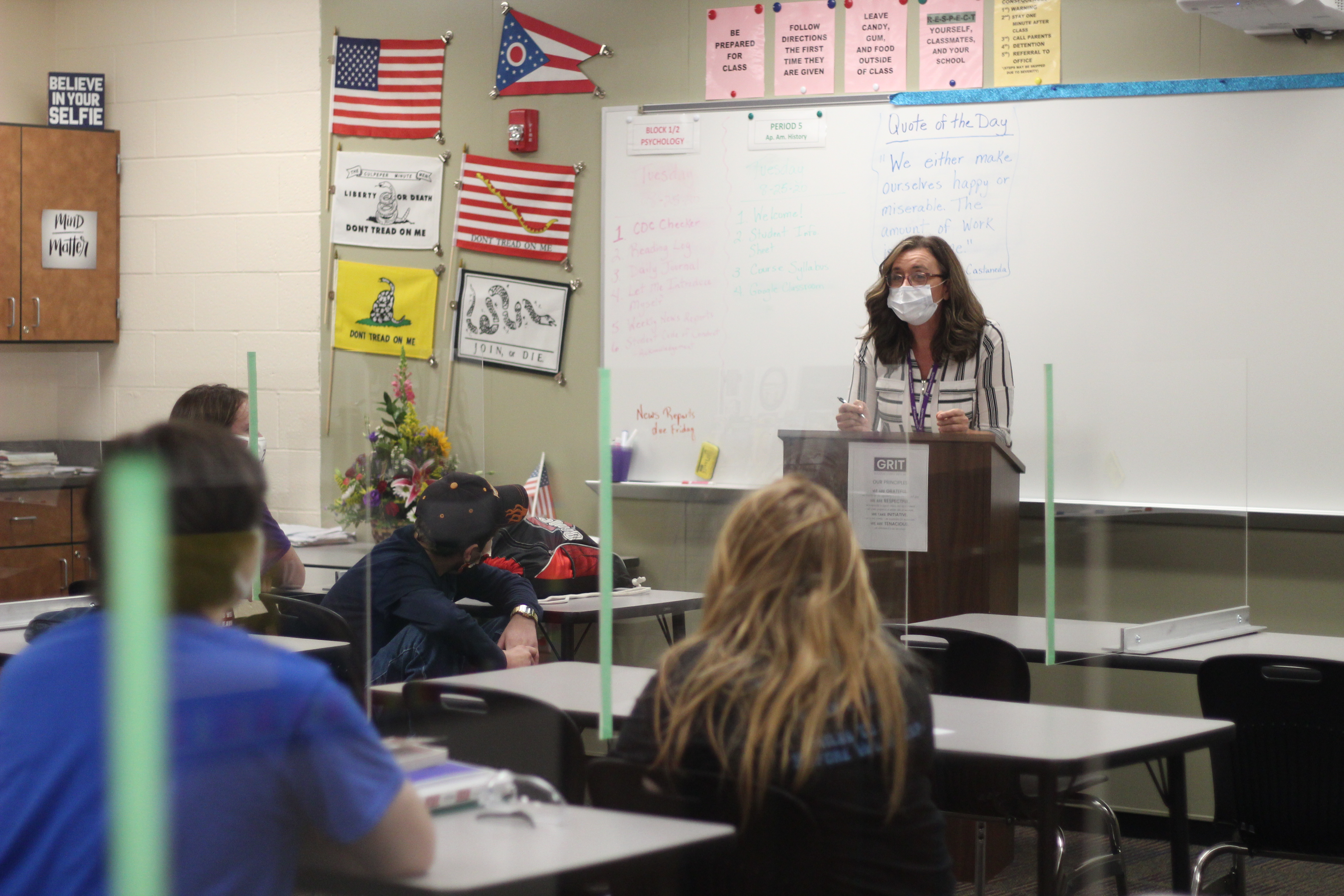 A female teacher in a white and gray striped shirt leans on a podium. She is wearing a white mask. Students are seated behind desks with plexiglass dividers.