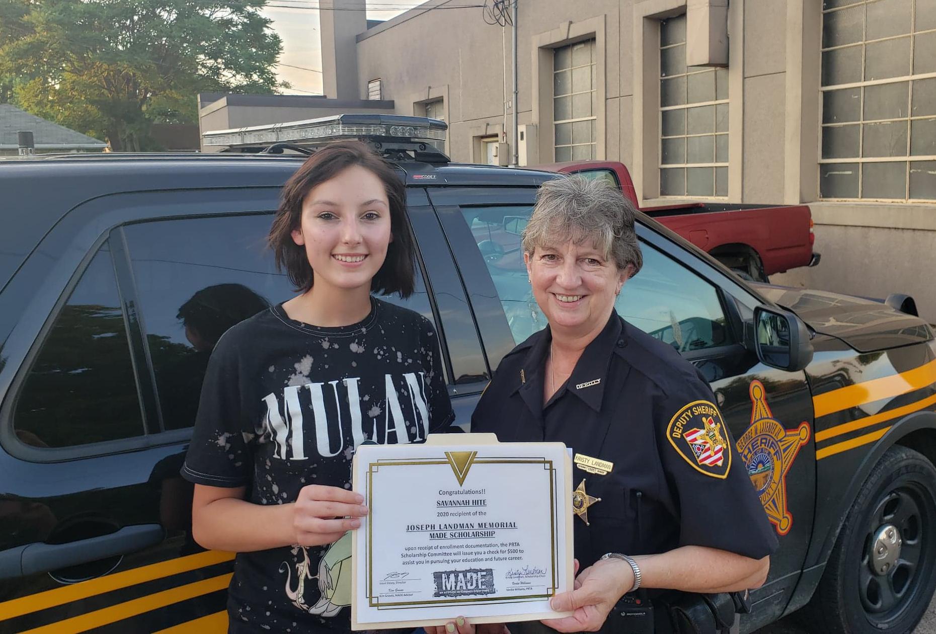 Savannah Hite, left, receives her scholarship certificate from Kristy Landman.