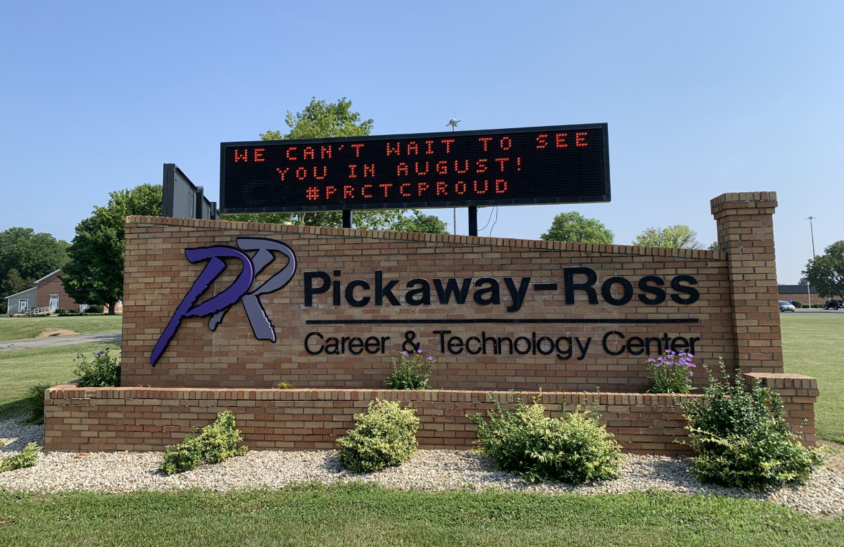 Image of sign at front campus. Sign text welcomes students back in August.